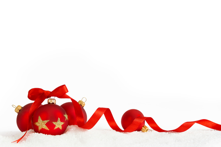 Four Christmas balls with red ribbon on artificial snow flakes.