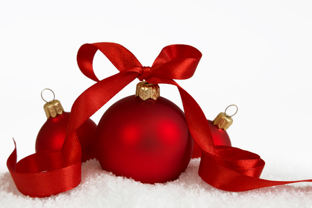 Three Christmas balls with red ribbon on artificial snow flakes.