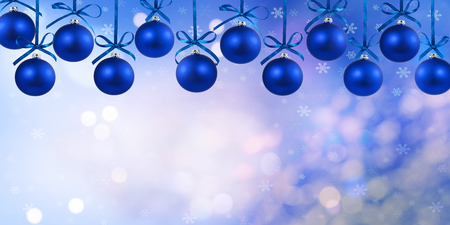 Christmas blue balls with ribbons isolated on defocused background