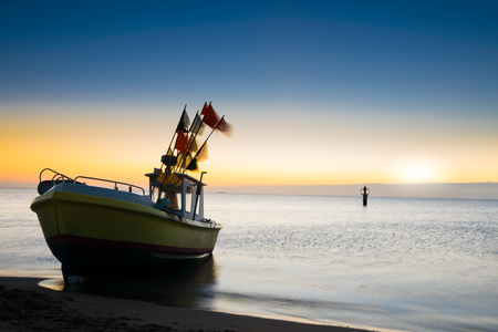 The rising sun illuminates the fishing boat. Baltic sea. 版權商用圖片