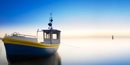 The rising sun illuminates the fishing boat. Baltic sea. Long exposure