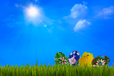 Easter decoration with colorful painted eggs and chicken under blue sky