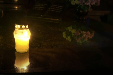 Burning candles at a cemetery before All Saints Day (1st November).