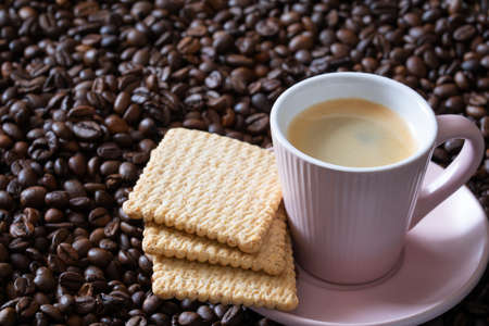 Cup of hot espresso coffee and biscuits on coffee beans dark background. Banque d'images