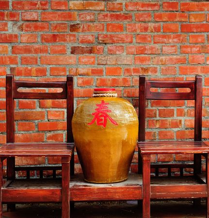 chinese jar and chair in fornt of brick wall