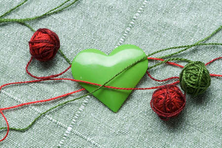 The green iron heart with the three clews on the cloth background Stock Photo - 4067618