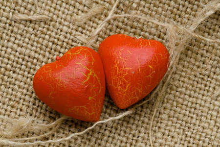 Two red hearts lie on the rough cloth photo