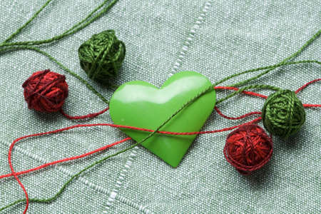 faithlessness: The green iron heart with the four clews on the cloth background Stock Photo