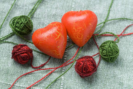 faithlessness: Two red hearts with the four clews on the cloth background Stock Photo