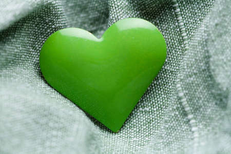 faithlessness: Green iron heart shape on the textile background