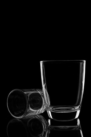 Pair of water glass and differenr size in isolated black background. photo