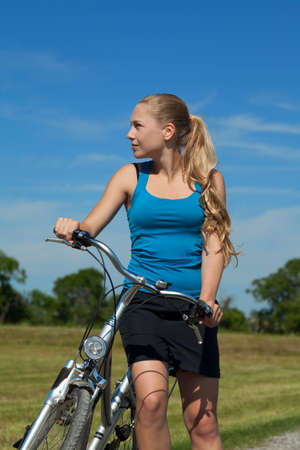 Blonde young woman with her bicyle outside photo