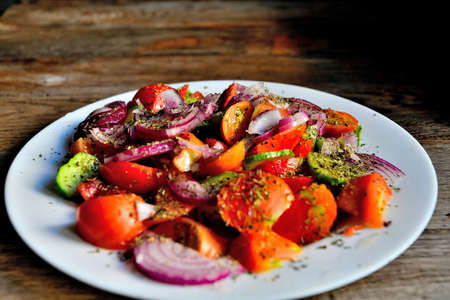 Summer salad of tomatoes, cucumbers, spices, and herbs on a white plate on a wooden table.