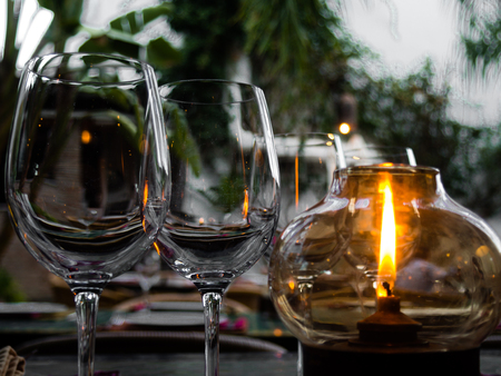 candle lights: Lighting crystal glasses by a candle in Garden Stock Photo
