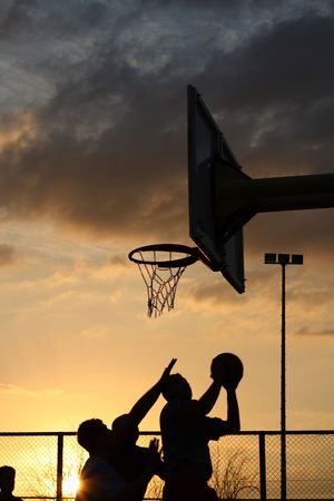 silhouettes of basketball players at the sunset photo