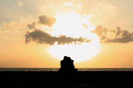 pareja abrazada: un joven sentado junto a la puesta del sol