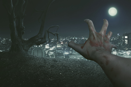 rising dead: Halloween Concept,  The point of view of the zombies right hand, with the background of an old tree and a city lit by the light of the full moon.
