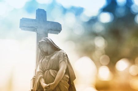 Het beeld van de Maagd Maria leunt tegen het Kruis met een lichte vervaging achtergrond. Stockfoto