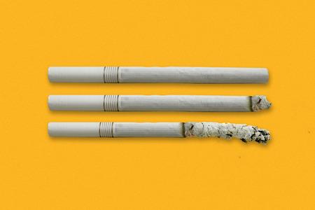 Close up of Cigarette isolated on orange background.