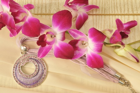 Necklace with flowers on a beige silk photo