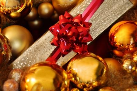 Gift box among christmas balls