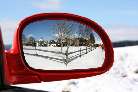 Landscape reflected in the rear view mirror of a red car photo