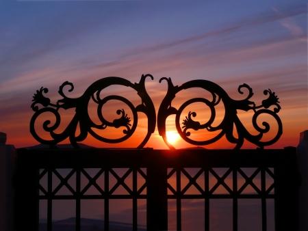 sunset   sunrise through iron gate on a cliff Stock Photo