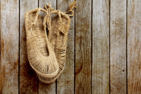 Vintage Chinese straw shoes on wooden wall Stock Photo