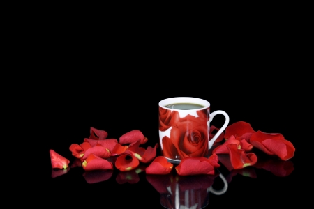 black rose: Red coffee cup among rose petals on the black background Stock Photo