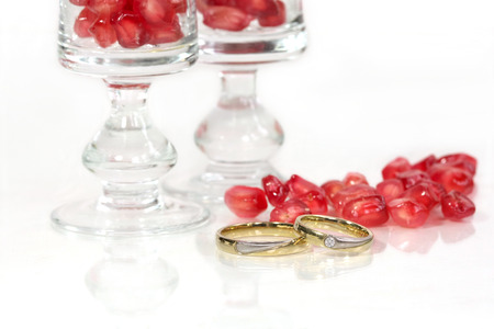 Marriage rings with red pomegranate at the background photo