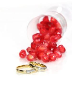 Marriage rings with red pomegranate at the background Stock Photo - 24532453