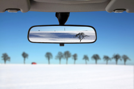 front side: Snow landscape reflected in the car rear view mirror