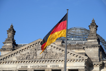 Swinging German flag with Bundestag at the background Stock Photo