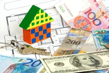 investment real state: Casa de madera colorida y teclas en diversas monedas y plan de arquitectura