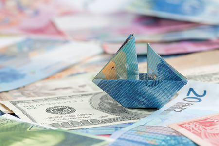 Swiss france folded as boat on world currencies - symbol of strong Swiss francs and other currencies with sinking values.