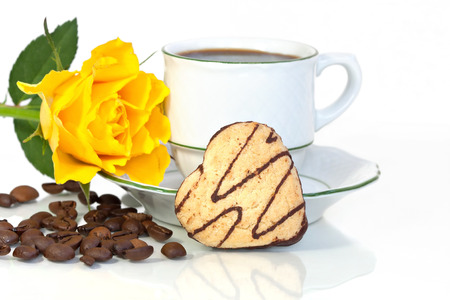 A heart shaped cookie beside a coffee cup, a yellow rose and some coffee beans