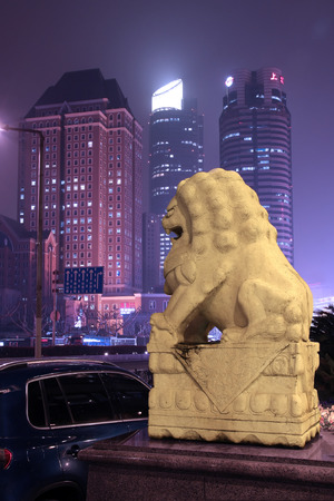 traditional stone lion with skyscrapers at the background Editorial