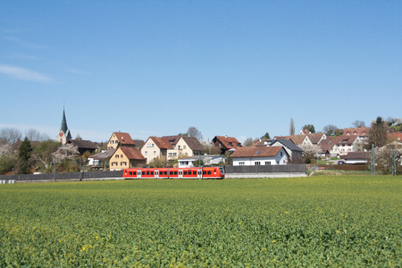 A red commuter train is crossing the countryside Stock Photo