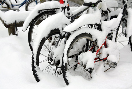 Snow covered bicycles in the street