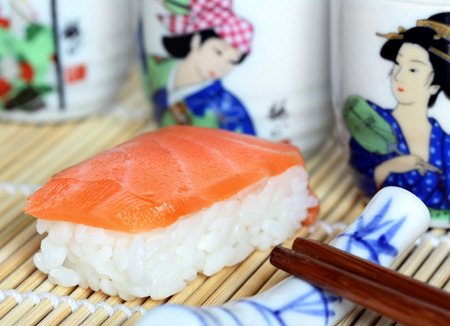Fresh salmon Sushi with saki cups and chopsticks Stock Photo
