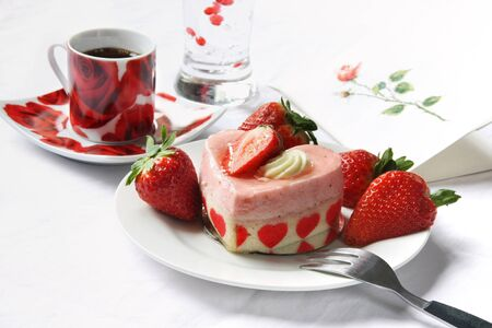 Heart shaped cake with fresh strawberry decoration and coffee