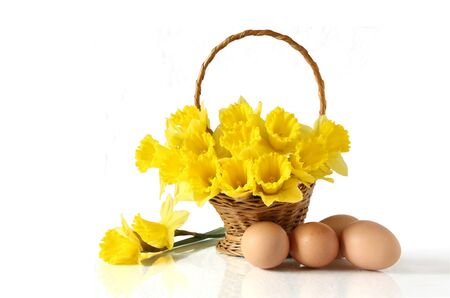 Daffodils in basket with Eastern eggs against white background Stock fotó