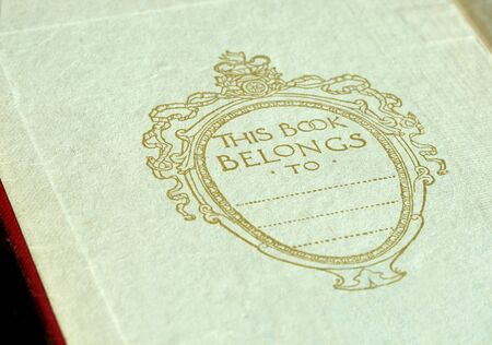 Inside Cover of an antique, yellowed book with script of belonging to Stock fotó