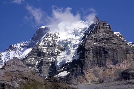 Swiss mountain summit: Jungfrau wrapped in clouds Stock Photo - 136872298