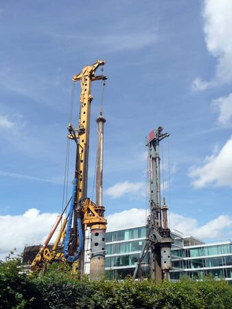 Two drill rigs on the construction site with a modern building in the background Stockfoto