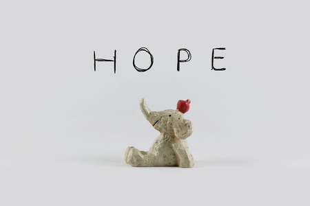 statue toy of smiling elephant with apple looking up over hope wordings background. Idea of happy, warm message concept for pattern background, card, decoration wallpaper, design template