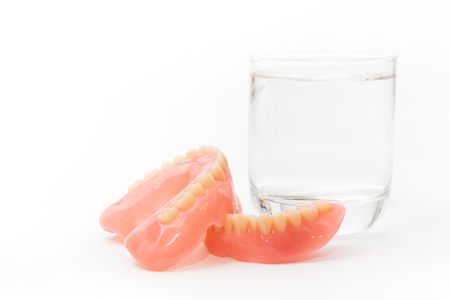 a denture is cleaned in a glass of water. proper hygiene. Banque d'images