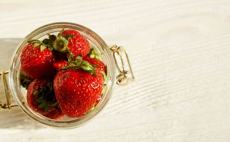 big red sweet strawberry in a glass jar on a wooden table