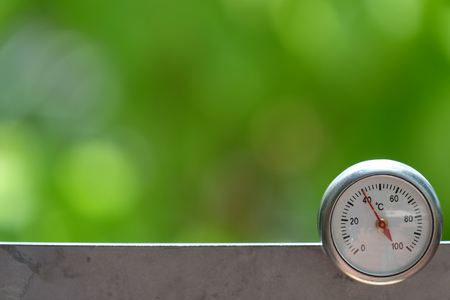 Circular celsius thermometer with green blurred background, Reverse concept