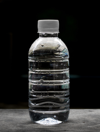 Plastic water bottle on wooden floor black background.